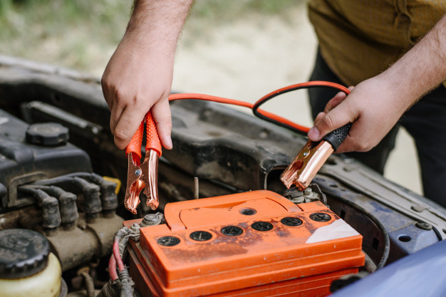 putting jumper cables on an orange car battery